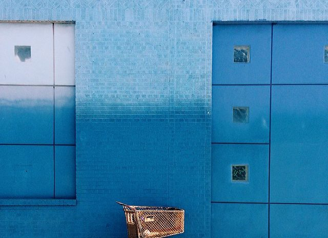 shopping cart against blue wall