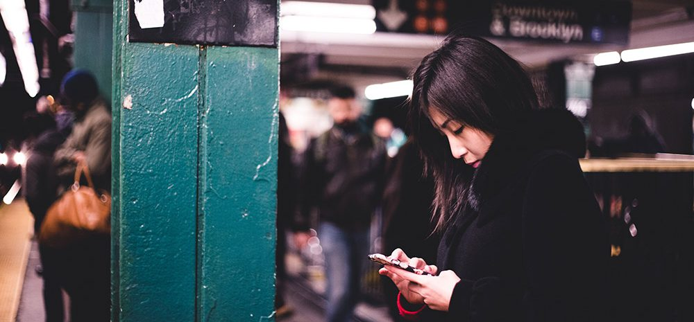Woman using mobile phone in a subway