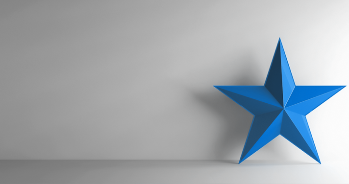 Blue star leaning on white wall