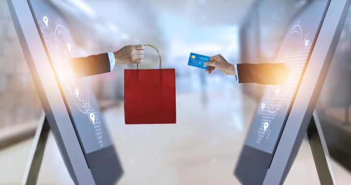 e-commerce, hand holding shopping bag and credit card from screen and global network