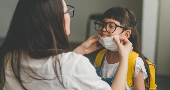 Mother helps her daughter wearing face mask for protection Coronavirus outbreak